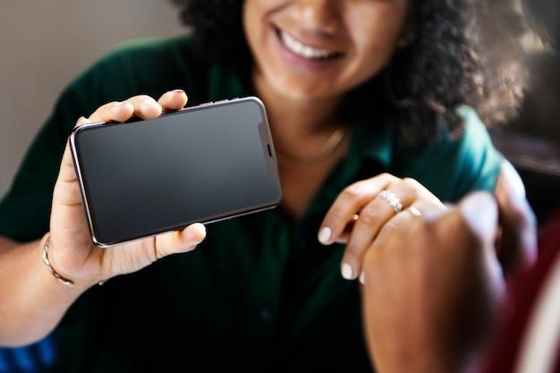 Femme montrant un téléphone vide