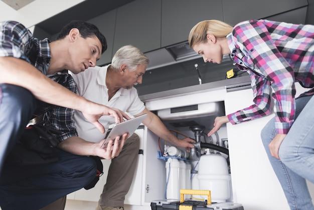 Une femme montre aux plombiers un évier de cuisine cassé