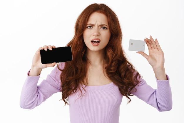Une femme montre un écran de smartphone horizontal et une carte de crédit, fronçant les sourcils et l'air déçue, se plaignant de quelque chose au téléphone, debout sur blanc