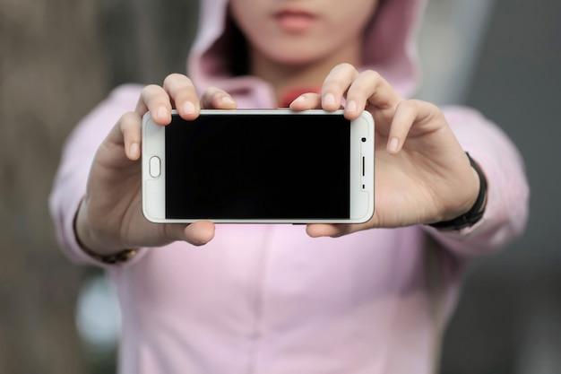 Une femme montre un écran tactile mobile