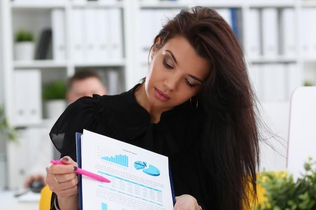 La femme montre le graphique de statistiques coupé au pad en portrait de bureau.