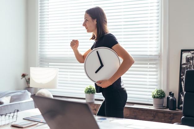 Une femme avec une montre à la main court vers ou depuis le travail.