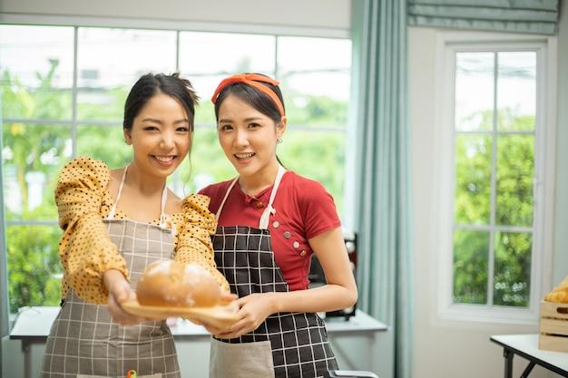 Une femme montre un pain qu'elle a fait à son amie.