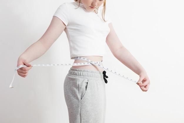 Femme montre une perte de poids sur fond de mur blanc