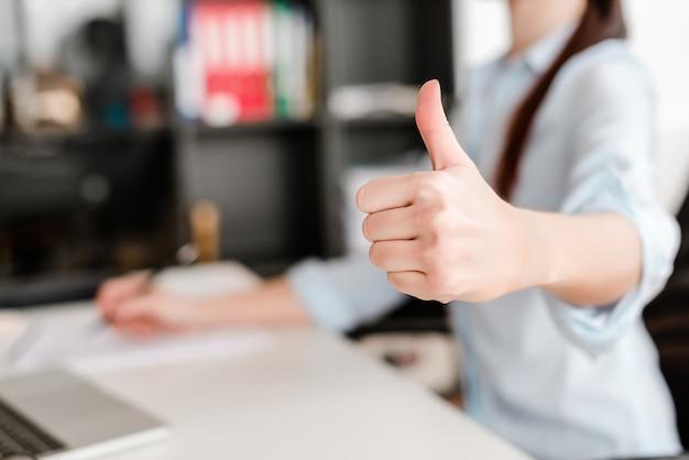 Femme montre pouces au bureau sur un lieu de travail