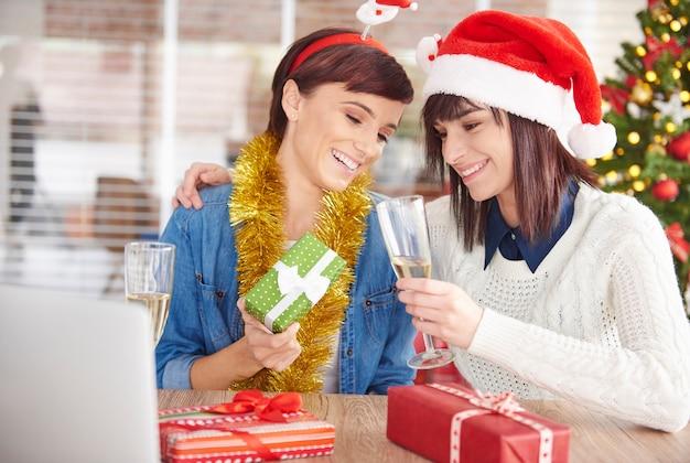 Une femme montre son cadeau de noël à un ami