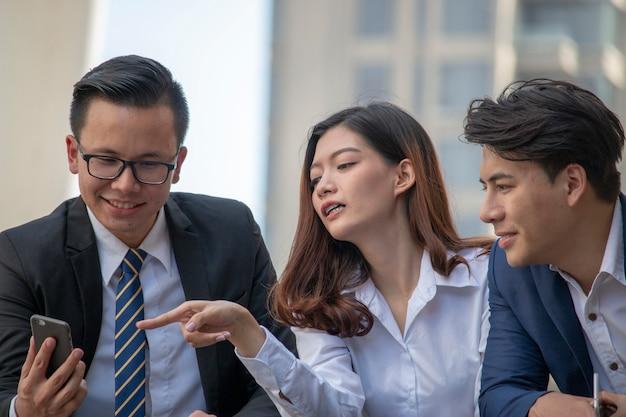 Une femme montre un téléphone portable avec deux hommes qui regardent