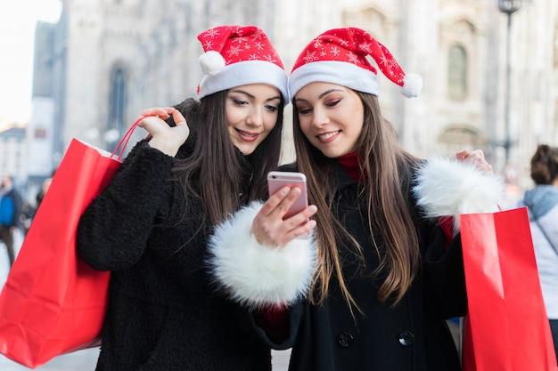 Une femme montre sur un téléphone portable quelque chose à son amie lors de ses achats à milan