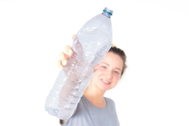 Femme montre et tenant une bouteille en plastique recyclable isolé sur fond blanc. collecte séparée des déchets.
