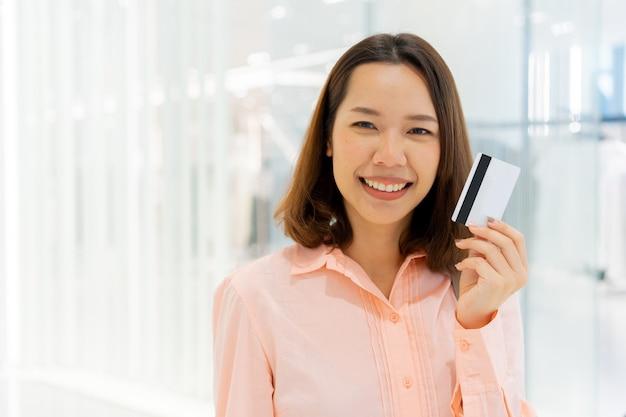 Femme montrer carte de crédit pour faire du shopping