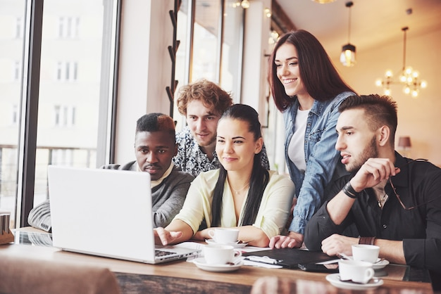 Femme, montrer, quelque chose, collègues, quelque chose, sur, ordinateur portable, comme, elles, rassemblent autour d'une table conférence