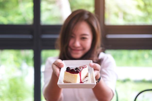 Femme et un morceau de gâteau au fromage aux bleuets