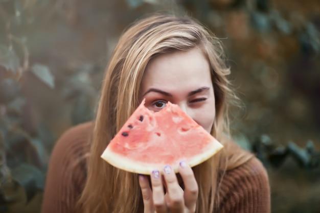 Femme avec un morceau de melon d'eau mûr dans une main lors d'un pique-nique.