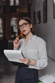 Femme mord un crayon et réfléchit à une nouvelle idée d'entreprise. portrait d'employé de bureau en chemisier blanc avec des documents en main.