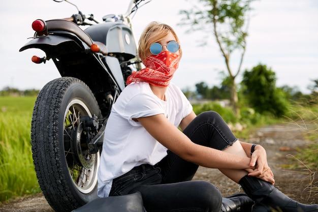 Femme motard assis à côté de la moto