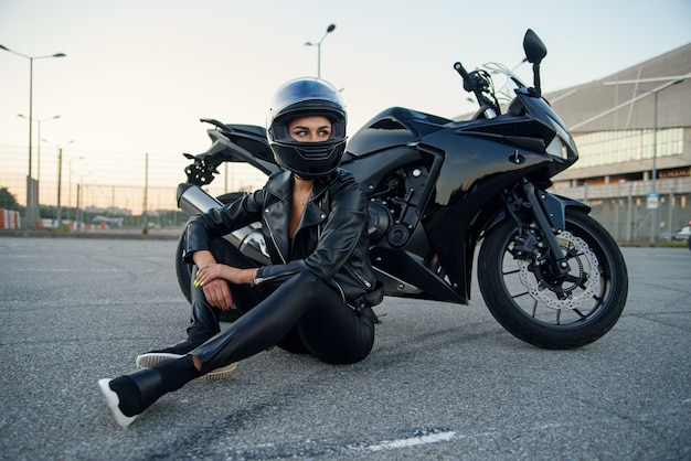 Femme de motard en veste de cuir noir et casque intégral se trouve près d'une moto de sport élégante au parking urbain. concept de voyage et de mode de vie actif.
