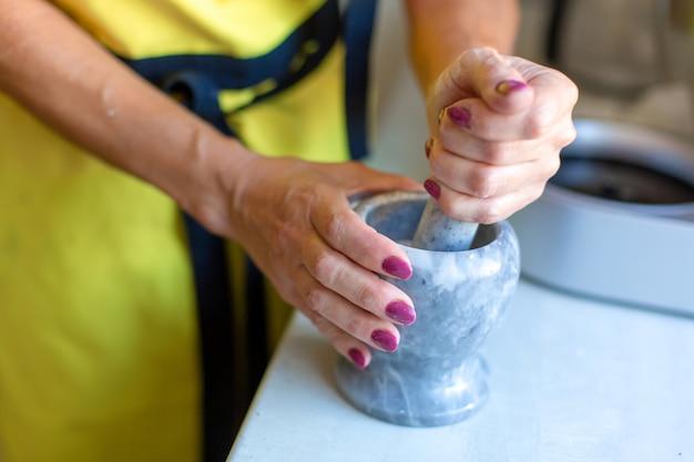 Une femme moud des noix dans un mortier. fabrication d'assaisonnement