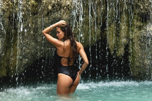 Femme mouillée dans une belle cascade avec de l'eau bleue
