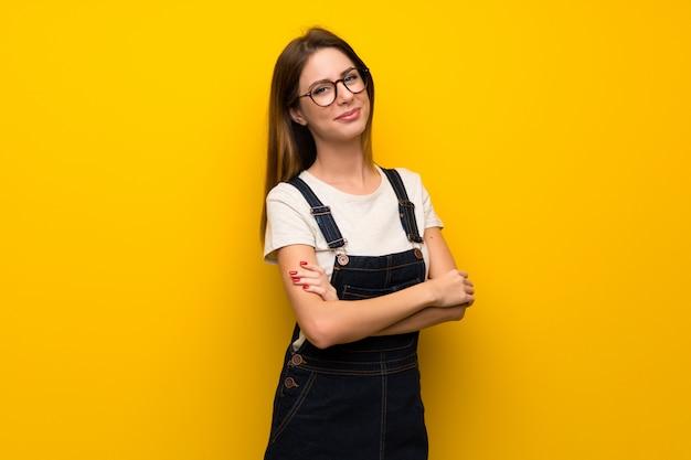 Femme sur un mur jaune avec les bras croisés et avec impatience