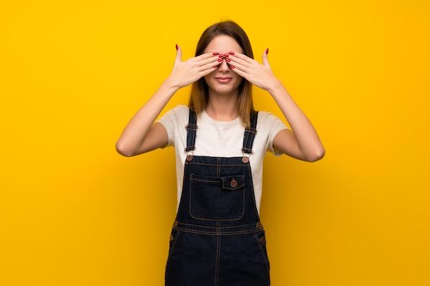 Femme sur mur jaune couvrant les yeux à la main. surpris de voir ce qui nous attend