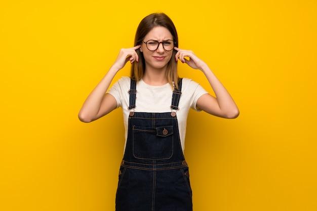 Femme sur un mur jaune frustré et couvrant les oreilles avec les mains