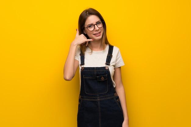 Femme sur mur jaune, geste de téléphone. rappelle-moi