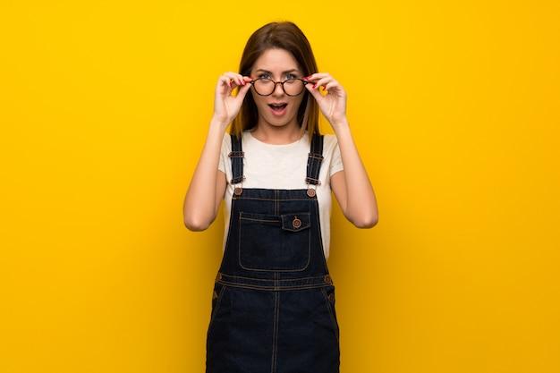 Femme sur un mur jaune avec des lunettes et surpris
