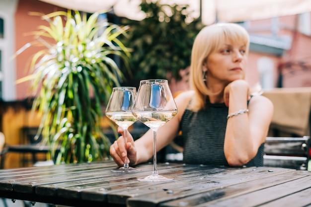 Une femme mûre adulte réfléchie assise dans un bar à l'extérieur avec des verres à vin et un restaurant flou