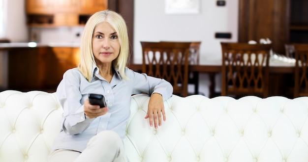 Femme mûre assise sur un canapé et utilisant la télécommande du téléviseur