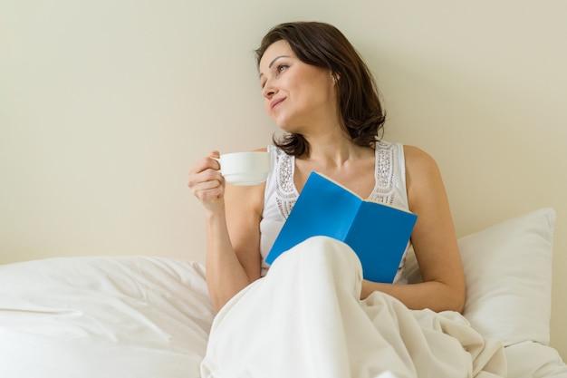Femme mure au lit, lecture de livre et boire du café