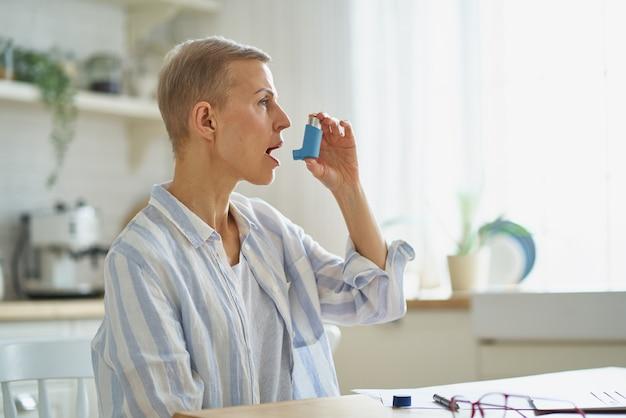 Femme mûre ayant une crise d'asthme alors qu'elle était assise dans la cuisine à la maison à l'aide d'un inhalateur
