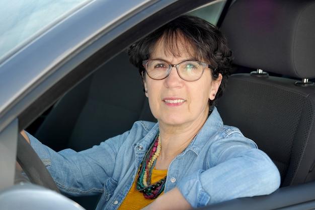Femme mûre brune conduisant une voiture