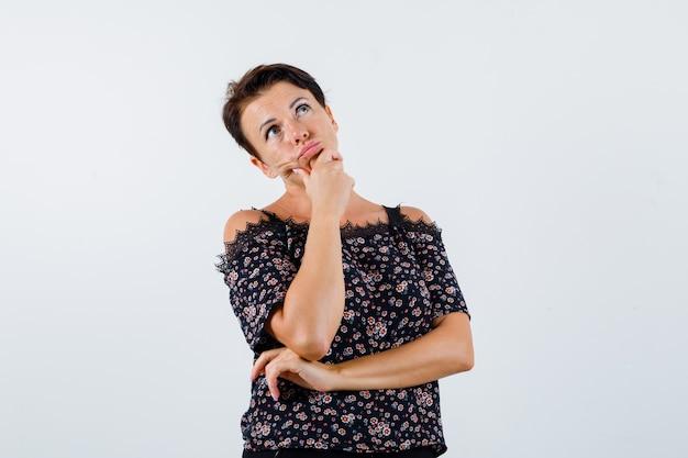 Femme mûre en chemisier floral, jupe noire appuyée sur le menton de la paume, pensant à quelque chose et à la recherche pensive, vue de face.