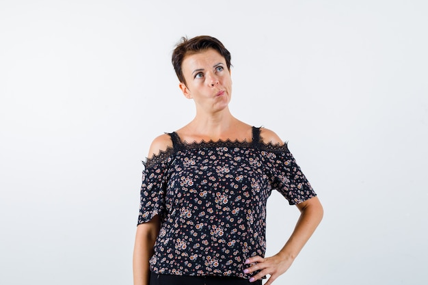 Femme mûre en chemisier floral, jupe noire, lèvres incurvées, tenant la main sur la taille et regardant pensif, vue de face.