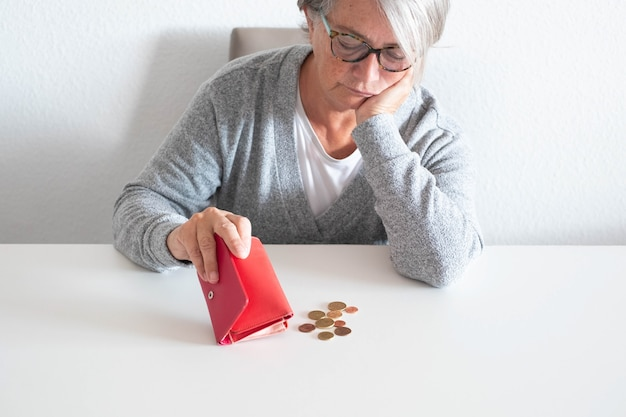 Une femme mûre compte l'argent qu'elle a moins pour le blâme de la crise du covid-19 ou du coronavirus - une personne âgée perd son emploi sans quitter sa maison pour la pandémie