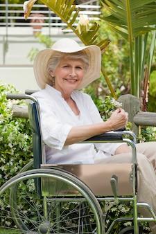 Femme mûre dans son fauteuil roulant dans le jardin