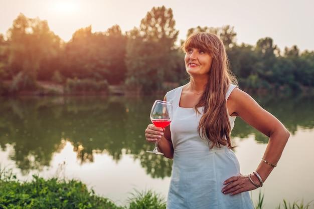 Femme mûre en dégustant un verre de vin au bord d'une rivière dans un parc en automne,