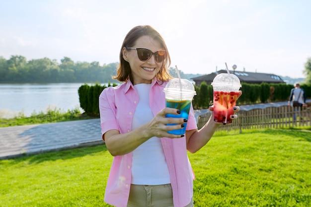 Femme mûre avec deux verres dans ses mains. zone verte de loisirs et de divertissement près de la rivière, espace de copie, heure d'or