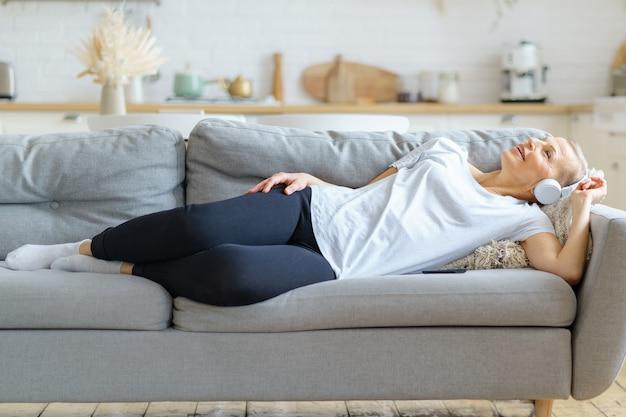 Femme mûre écoutant de la musique dans des écouteurs allongés sur un canapé et rêvant les yeux fermés