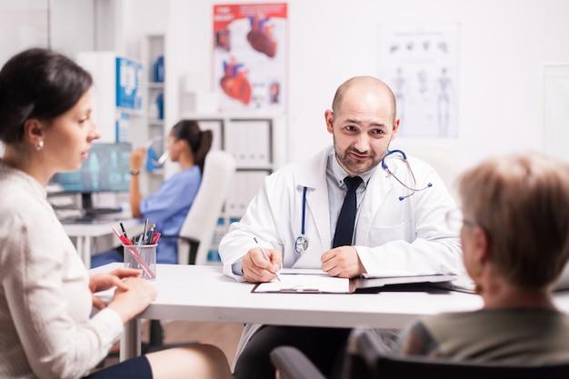 Femme mûre avec un handicap de marche en fauteuil roulant avec sa fille lors d'un examen médical avec un médecin au bureau de l'hôpital. medic écrit des notes sur le presse-papiers et l'infirmière travaille sur ordinateur.