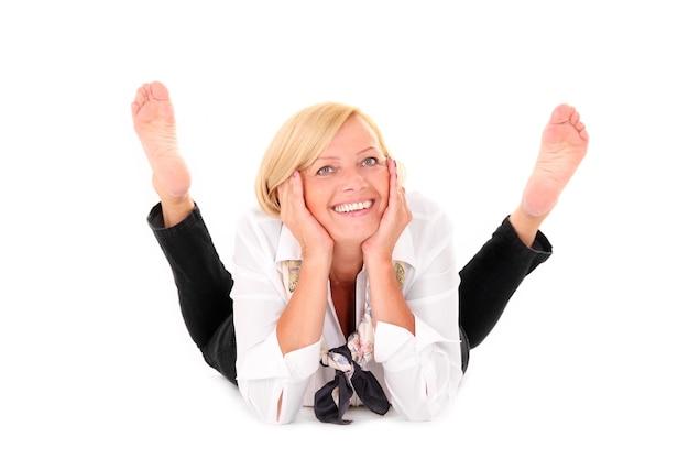 Une femme mûre heureuse allongée sur fond blanc