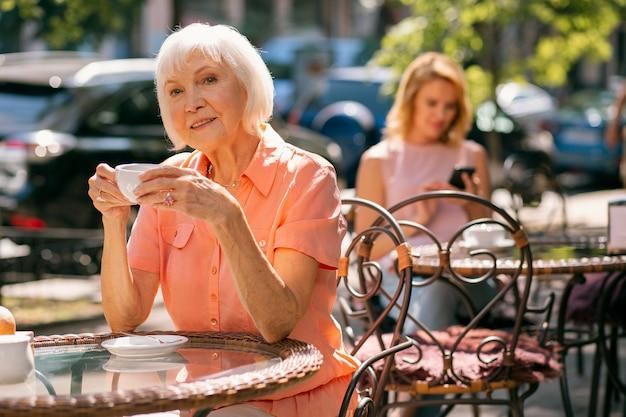 Femme mûre joyeuse se détendant dehors avec une tasse de café chaud