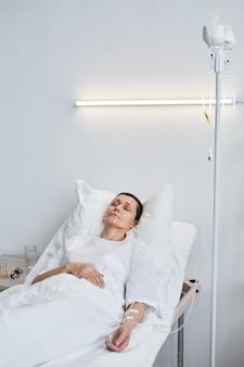 Femme mûre malade allongée sur le lit avec les yeux fermés sous le goutte-à-goutte à l'hôpital
