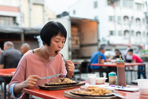 Une femme mûre mange un steak de marché de nuit taïwanais dans la rue
