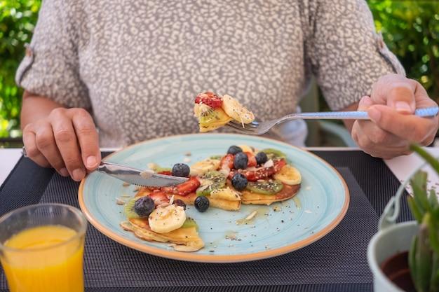 Femme mûre mangeant le petit déjeuner sain d'été, les crêpes américaines classiques avec la banane, le kiwi, la baie fraîche et le miel