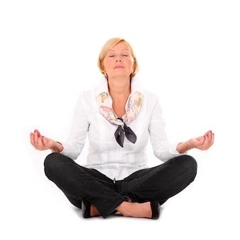 Une femme mûre pratiquant le yoga sur fond blanc