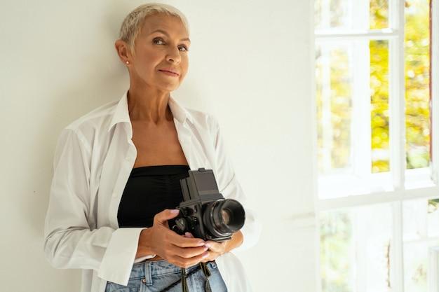 Femme mûre ravie s'appuyant sur le mur tout en créant de nouvelles idées pour la prise de vue