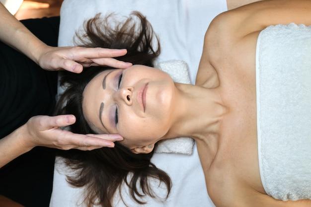 Une femme mûre reçoit un massage du visage et du cou au salon de beauté spa. cosmétologie, traitement, soins de santé, soins de la peau du visage et du corps, femmes d'âge moyen