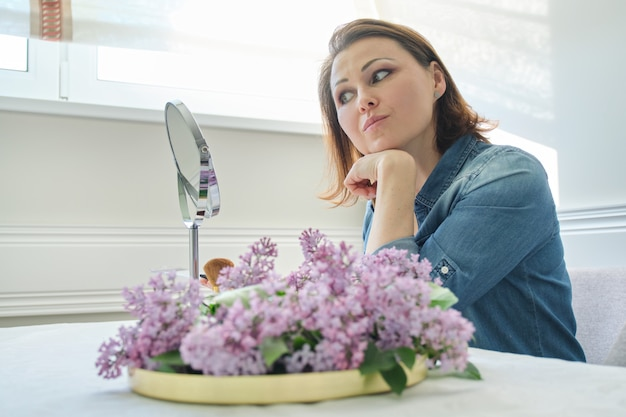 Femme mûre en regardant son visage dans le miroir
