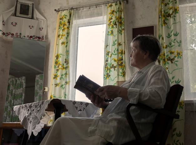 Femme mûre resti avec livre dans un fauteuil dans le salon avec un design d'intérieur du milieu du...
